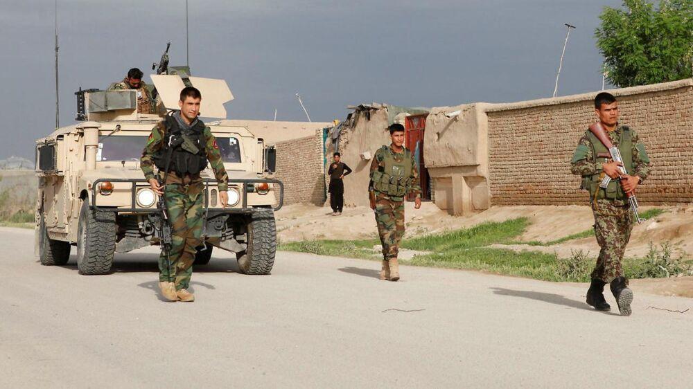 Soldater fra Afghanistans hær ankommer til basen under angrebet.