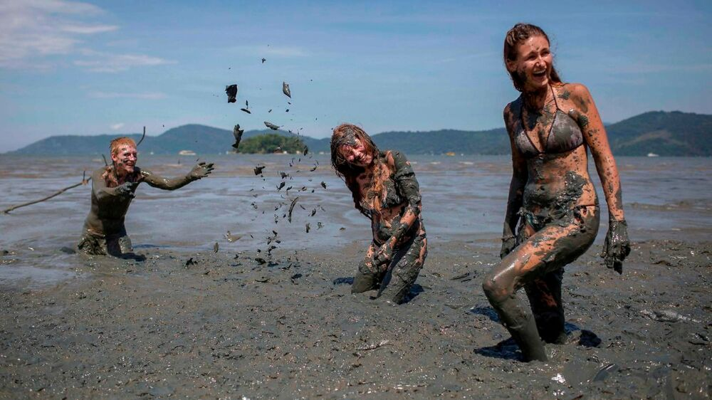 "Revellers celebrate during the ""Bloco da Lama"", a mud carnival, in Paraty, Brazil, on February 10, 2018. ""Bloco da Lama"" started in 1986 by teenagers playing with mud and became a traditional event at the historical city of Paraty. / AFP PHOTO / MAURO PIMENTEL"