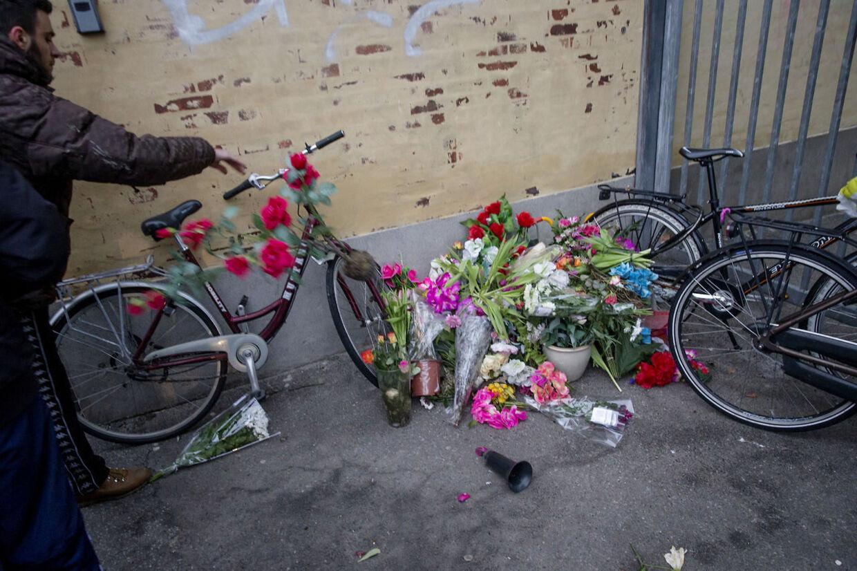Unge mænd fjerner blomsterne på stedet hvor den afdøde blev dræbt.