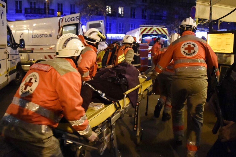 Franske Røde Kors-medarbejdere er ved at tage sig af en såret person uden for koncertsalen Bataclan i Paris i France 14. november 2015.