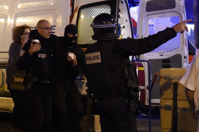 En såret politimand fra de franske specialstyrker får hjælp af en kollega. AFP PHOTO / DOMINIQUE FAGET