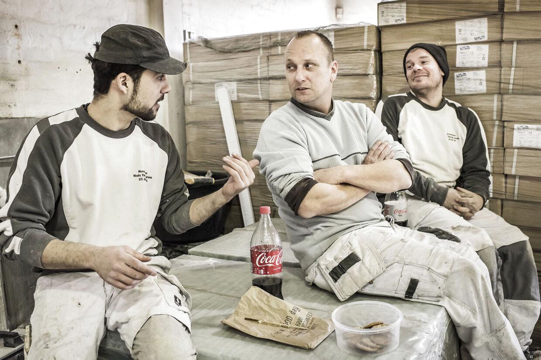 Reportage fra en arbejdsplads i Valby, hvor Mads Thorup Larsens murerfirma i øjeblikket arbejder på en kommende bilforhandler. Larsen har for seks måneder siden ansat Muhiddin Al-Sheikh, der er syrer, som fik asyl i Danmark for 1, 5 år siden. Frokostpause: Frank Larsen (midten) og Jakob Rolighed (th) spiser baby-bites, mens Muhiddin Al-Sheikh får kyllingespyd.