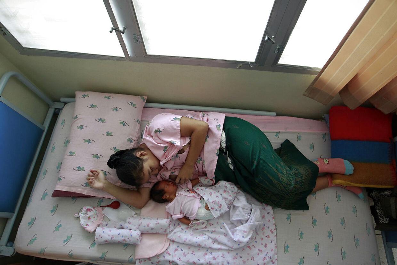 Tidlige ægteskaber og børn er ikke ualmindelige i Thailand. Her giver en 14-årig mor sit en uge gamle baby bryst på en hospital i Chiang Mai.