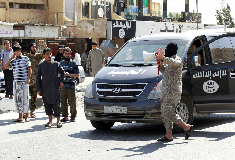 En Islamisk Stat-tilhænger proklamerer med en megafon den 24. august 2014, at IS har overtaget kontrollen med Taqba-luftbasen. Overtagelsen blev fulgt op af en massehenrettelse, der blev filmet og lagt på nettet. Arkivbillede.