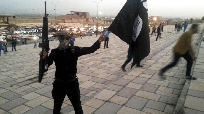 På billedet ses en IS-soldat med et våben og terrororganisationens karakteristiske sorte flag i Mosul i Irak i juni 2014.