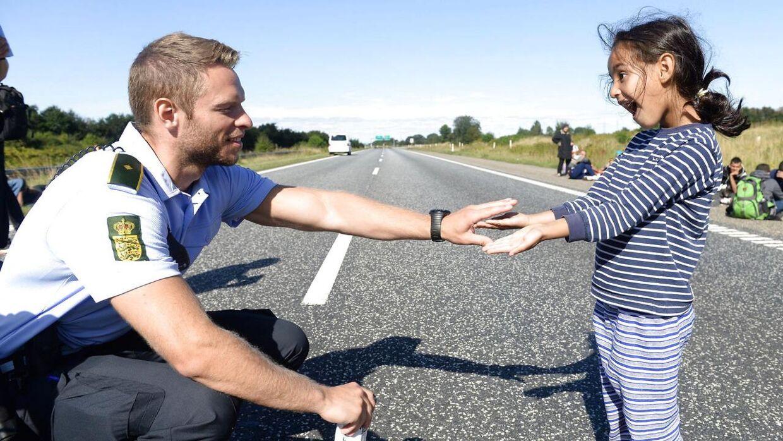 Her laver betjenten sjov med den syriske pige. Ifølge BTs fotograf, der har taget billedet, gemmer betjenten sin vielsesring i den ene hånd, så pigen skal gætte, hvor den er.