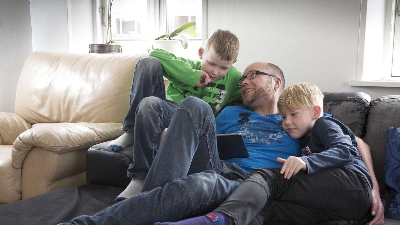 Allan Larsen sidder med sine to sønner Bastian og Alex i sofaen derhjemme. Drengene er lige kommet hjem fra skole.