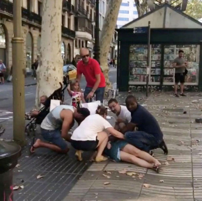 Lokale og turister er i fuld gang med at hjælpe en tilskadekommen kvinde på ramblaen.