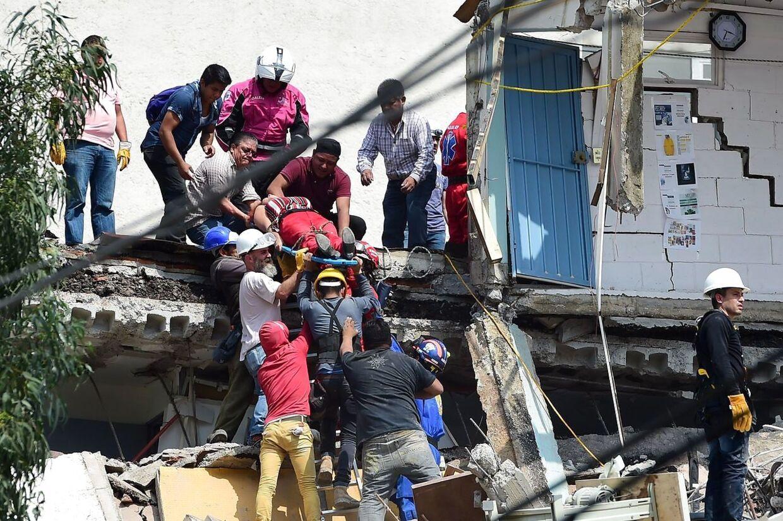 En tilskadekommen kvinde bæres her væk fra murbrokkerne efter et hus er faldet fra hinanden. Foto: AFP/ Ronaldo SCHEMIDT