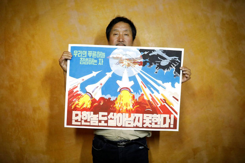 Leder af Galleri Pyongyang med én af de mange propagandaplakater, som Kim Jong-uns lillesøster står bag. 'Ingen invaderer vor blå himmel' står der på plakaten.
