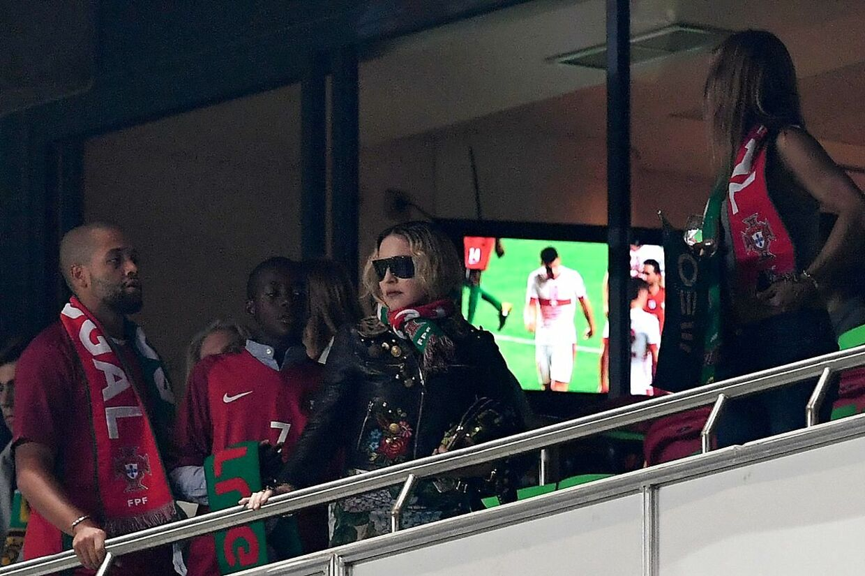 US pop star Madonna (C) and her son David Banda attend the FIFA World Cup 2018 Group B qualifier football match between Portugal and Switzerland at the Luz Stadium in Lisbon on October 10, 2017. / AFP PHOTO / FRANCISCO LEONG