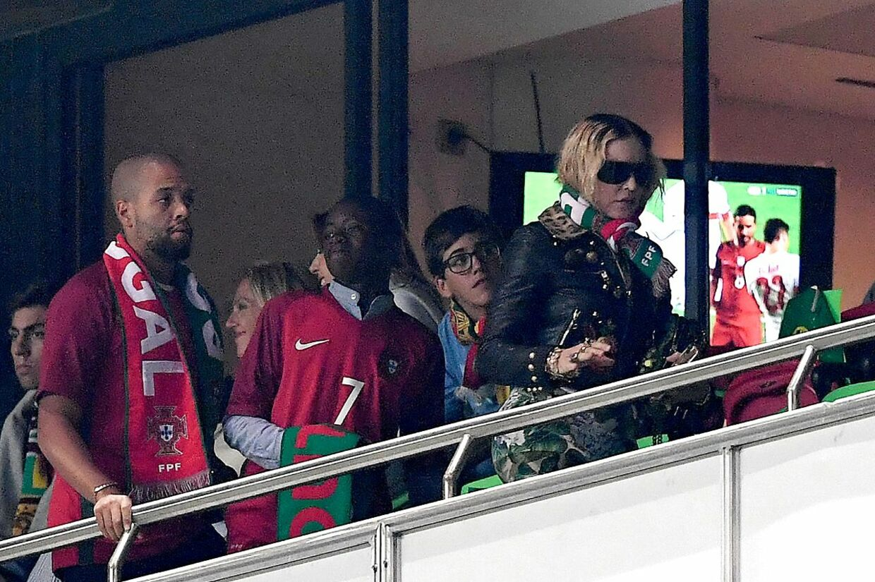 US pop star Madonna (R) and her son David Banda attend the FIFA World Cup 2018 Group B qualifier football match between Portugal and Switzerland at the Luz Stadium in Lisbon on October 10, 2017. / AFP PHOTO / FRANCISCO LEONG