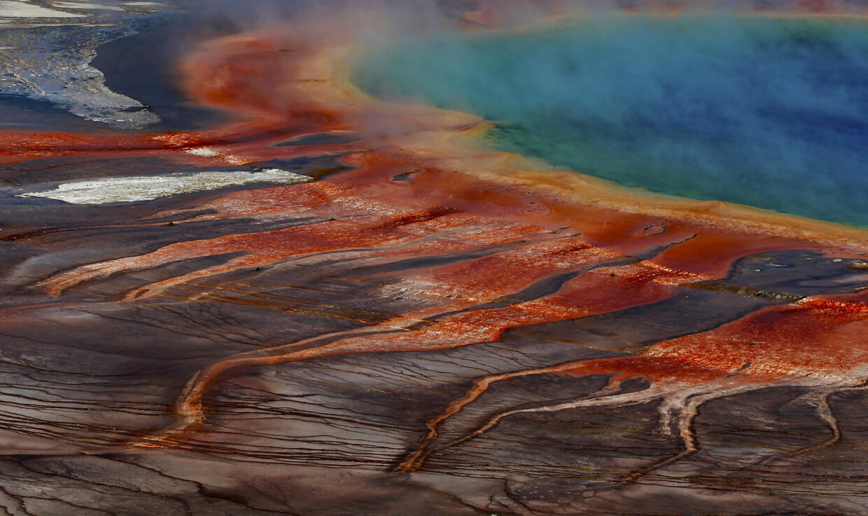 Kildens farvespil langs bredderne stammer fra pigmenterede bakterier, der lever langs kanten det mineralholdige vand.