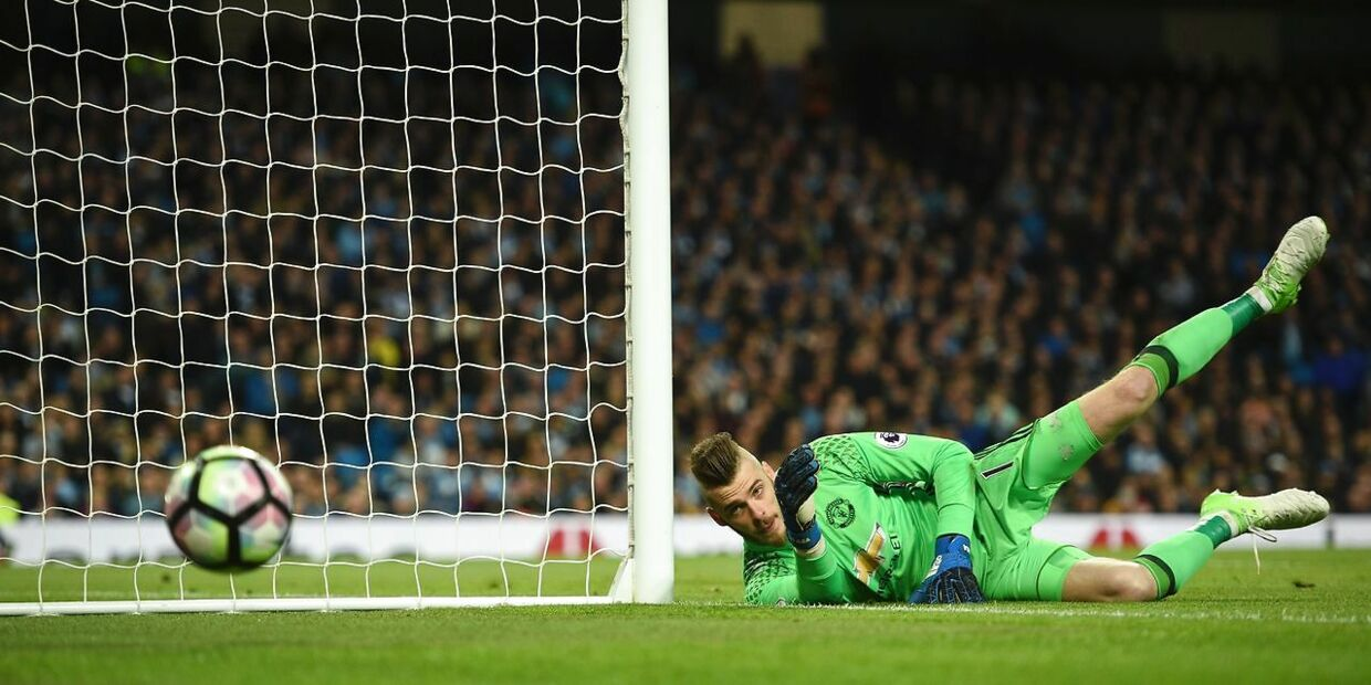 Manchester United's Spanish goalkeeper David de Gea (R) saves a shot during the English Premier League football match between Manchester City and Manchester United at the Etihad Stadium in Manchester, north west England, on April 27, 2017. / AFP PHOTO / Oli SCARFF / RESTRICTED TO EDITORIAL USE.No use with unauthorized audio, video, data, fixture lists, club/league logos or 'live' services. Online in-match use limited to 75 images, no video emulation.No use in betting, games or single club/league/player publications. /