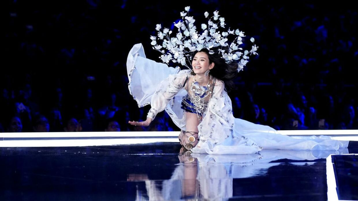 Model Ming Xi falder ned på alle fire under dette års Victoria's Secret Fashion Show i Shanghai.