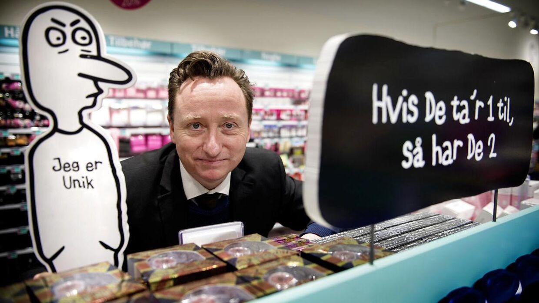 Søren Fauli ved siden af nogle af hans skilte med overraskende slogans i butikken Normal.