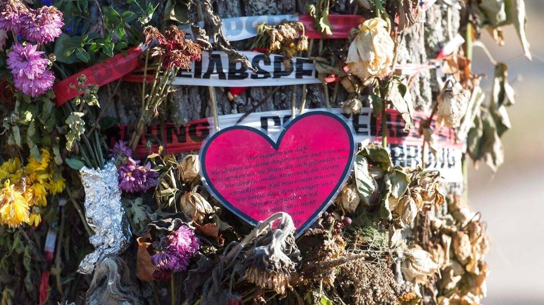 Blomster og kort på et træ ved det sted, hvor liget af den 19-årige kvinde blev fundet.