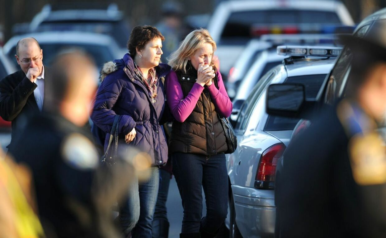 Sørgende pårørende foran grundskolen i Newtown efter fredagens tragiske massakre.