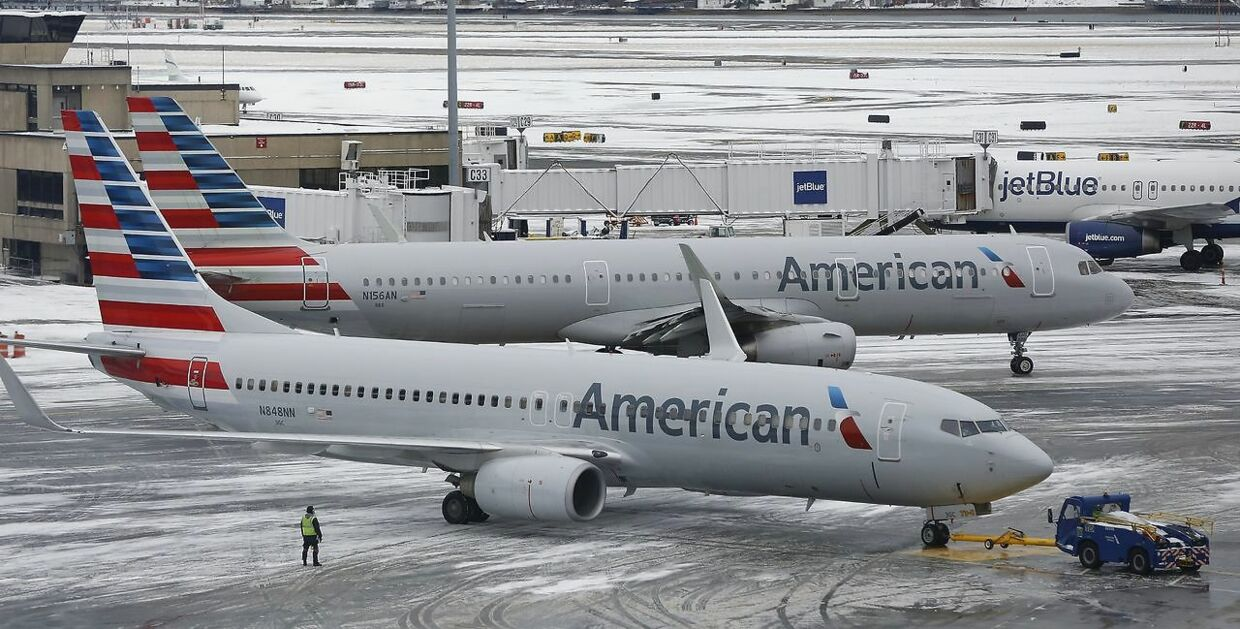 epa06486491 American Airlines passenger planes prepare for takeoff at Boston Logan International Airport in Boston, Massachusetts, USA 30 January 2018. A late January snowstorm left two inches (5cm) in the greater Boston area and caused several delays at the airport. EPA/CJ GUNTHER