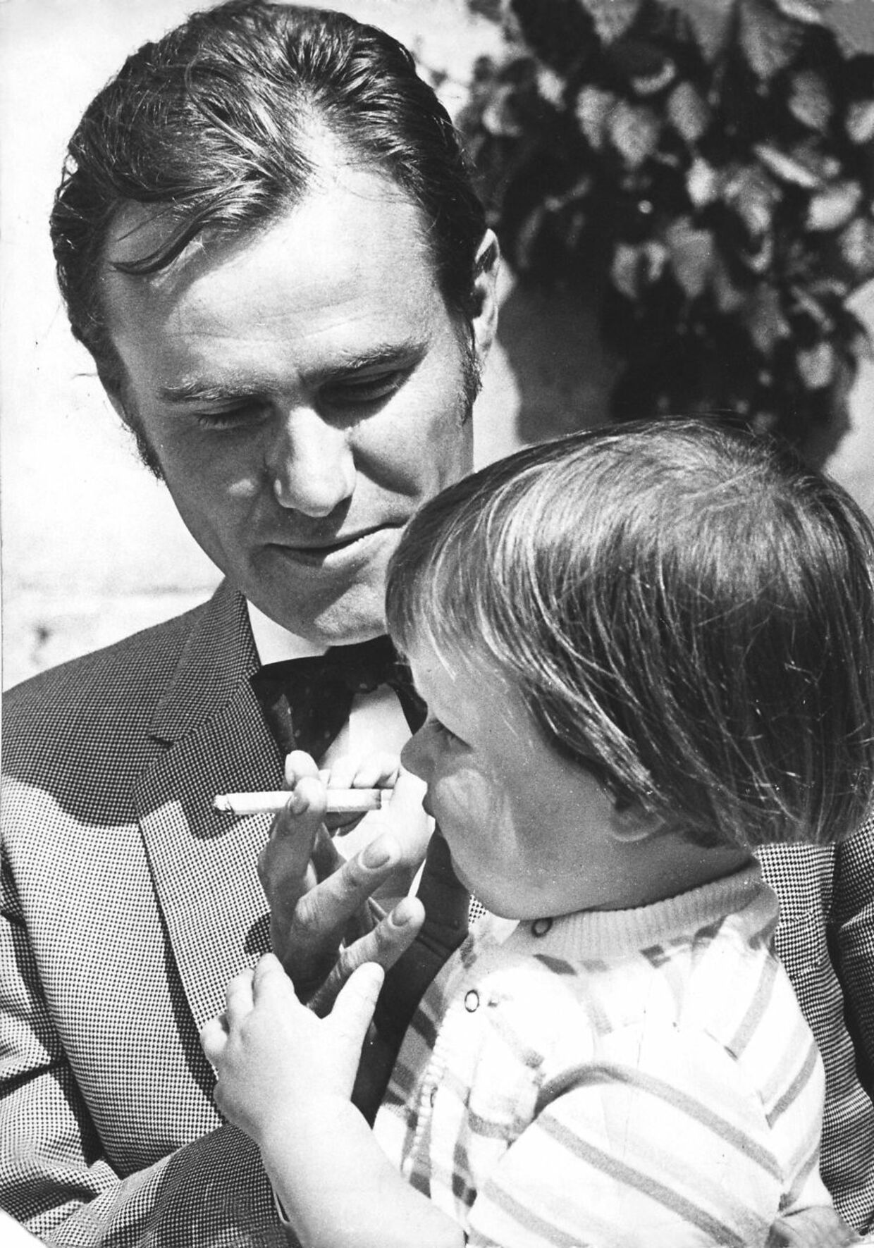 """""""Vil du have et hiv?"""" Prins Henrik med sin to-årige søn kronprins Frederik i haven bag ved Amalienborg i 1970."""