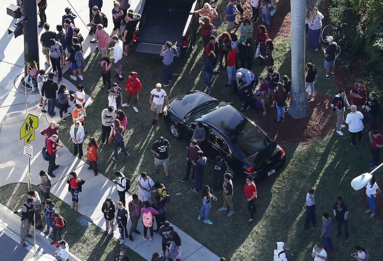 På billedet ses pårørende vente foran skolen Marjory Stoneman Douglas High School.