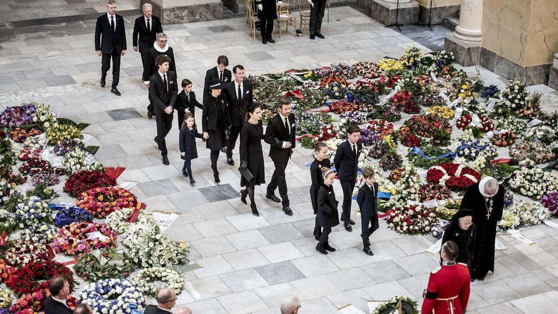 Kongefamilien ankommer til Prins Henriks bisættelse fra Christiansborg Slotskirke i København. Her går de mellem de mange blomster.
