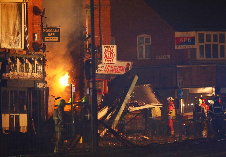 Redningsarbejdere leder efter personer i det sammenstyrtede hus.