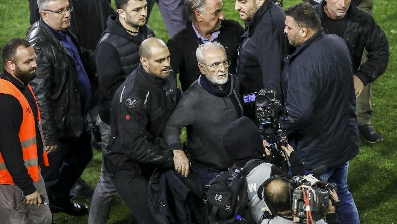 Ivan Savvidis (i midten) undskylder for at have invaderet banen med en pistol.