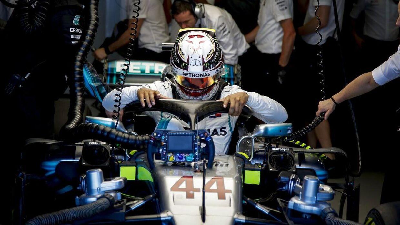 Lewis Hamilton er ikke tilfreds med den nye 'Halo', som han her har fat i, mens han sætter sig ned i sin Mercedes-racer.