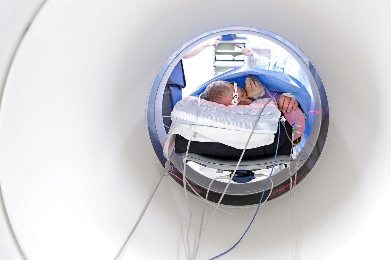 Poul Nielsen ligger i en CT-scanner. Han er bedøvet med nogle nye stoffer, der erstatter den traditionelle narkose, så lægerne hele tiden kan komme i kontakt med ham, hvis de vil.