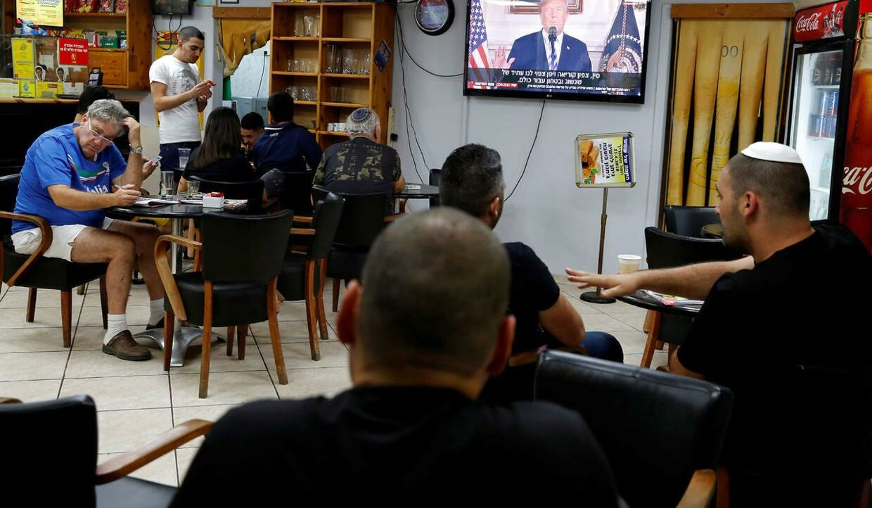 Israelere i en café følger Trumps tale på tv. Ashkelon i Israel, tirsdag aften. Den 8. maj.