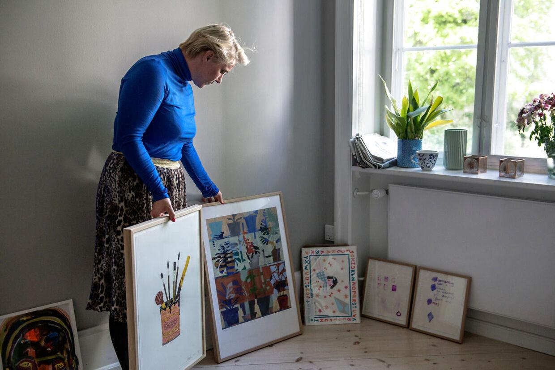 Mette Helena i gang med at indrette det nye beboerrum. Hun elsker kunst, og derfor bliver der hængt mange billeder på væggene.