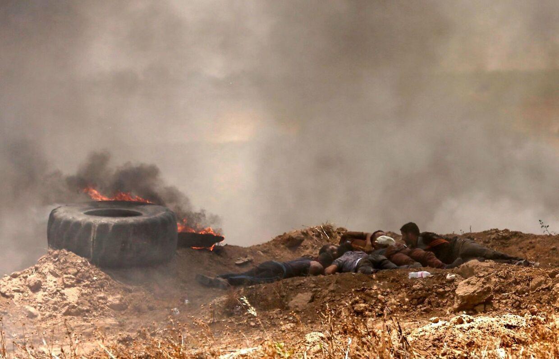 Palæstinensere søger dækning for skud fra israelske styrker.
