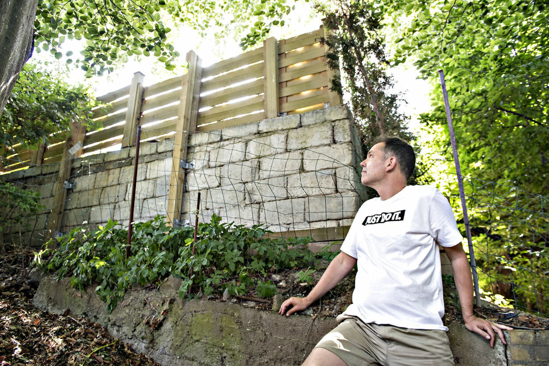 Søren Sørensen foran naboens støttemur, som først blev erklæret ulovlig af kommunen. Siden har kommunen valgt at kalde støttemuren en hegnsmur, så nu er den lovlig.