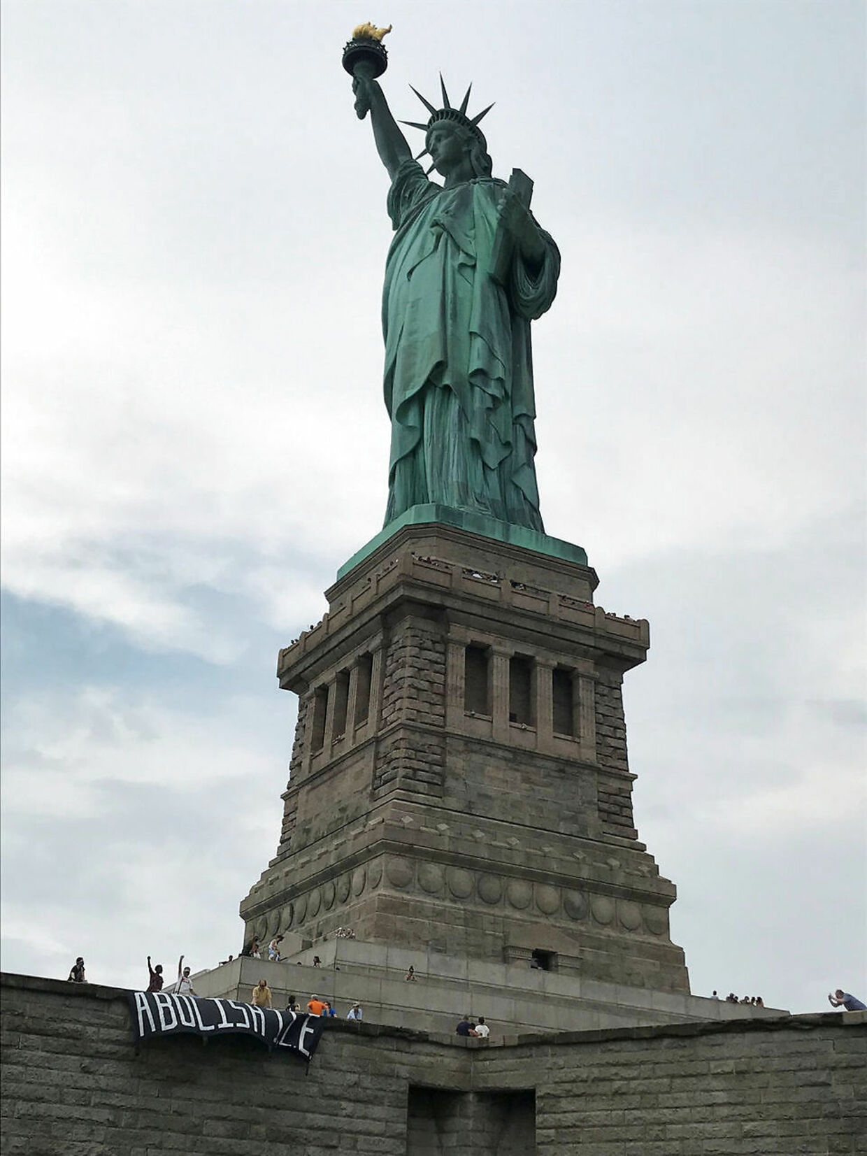 The group Rise and Resist stage a protest at the Statue of Liberty in New York, U.S. July 4, 2018 in this picture obtained from social media. Rise and Resist/via REUTERS ATTENTION EDITORS - THIS IMAGE HAS BEEN SUPPLIED BY A THIRD PARTY. MANDATORY CREDIT.NO RESALES.NO ARCHIVES.