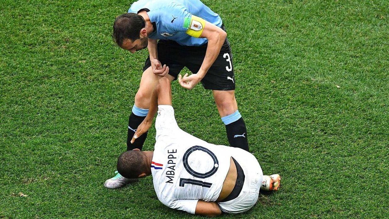 UruguaysDiego Godin konfronterer Mbappé efter situationen, men franskmanden rejste sig ikke med det samme.