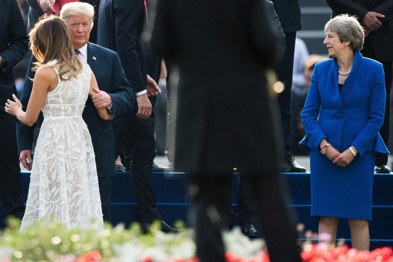 Ved Natotopmødet i Bruxelles spejder Storbritanniens premierminister, Theresa May (th), efter at USA's præsident, Donald Trump, og hustruen, Melania (tv). Trump kritiserer andre Natolande for at spare for meget på forsvaret. Benoit Doppagne/Ritzau Scanpix