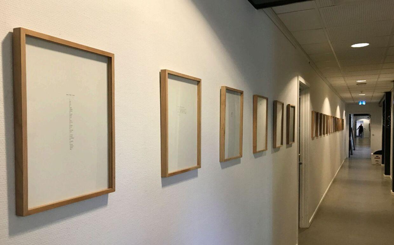 Disse 21 rammer med papirark med små noter på kostede Københavns Kommune 34.000 kroner. Kunstneren hedder Cia Rinne.