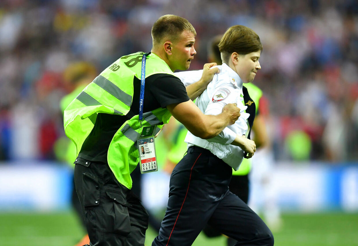 Soccer Football - World Cup - Final - France v Croatia - Luzhniki Stadium, Moscow, Russia - July 15, 2018 Stewards catch a pitch invader REUTERS/Dylan Martinez