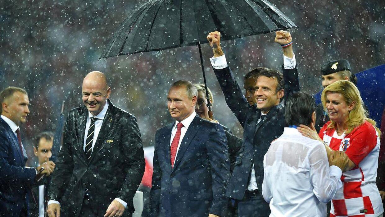 FIFA-præsident Gianni Infantino, Vladimir Putin og Emmanuel Macron i regnen. REUTERS/Dylan Martinez