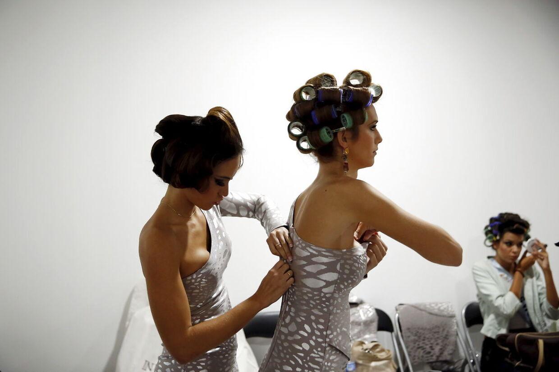 I 2015 deltog Angela Ponce i Miss World og vandt, men på grund af reglerne kom der ingen invitation til den internationale konkurrence. En konkurrent hjælper Angela med at få kjolen til at sidde helt rigtigt.