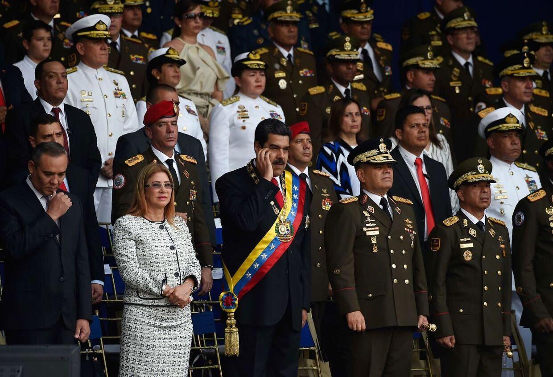 Venezuelas præsident, Nicolas Maduro (i midten) med sin hustru Cilia Flores (tv.) på scenen.