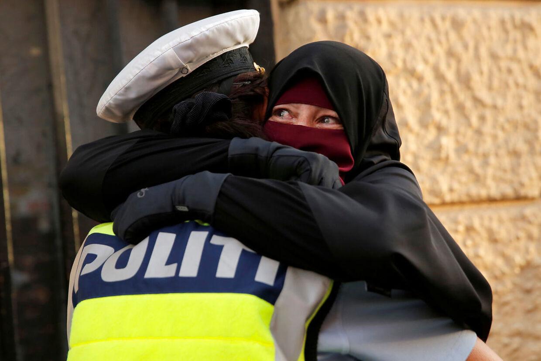 Tildækningsforbuddet vækker stærke følelser – også i politiet. Her får 37-årige Ayah et kram af en kvindelig betjent under en demonstration mod tildækningsforbuddet 1. august.