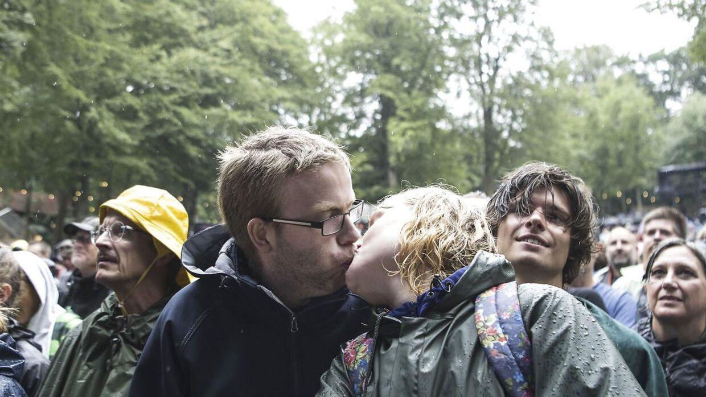 På trods af silende regn gennem store dele af den uge lange festival gav Smukfest-gæsterne ikke op. Her kysser et par, mens C.V. Jørgensen spiller på Bøgescenen på festivalens sidste dag søndag den 12. august 2018.