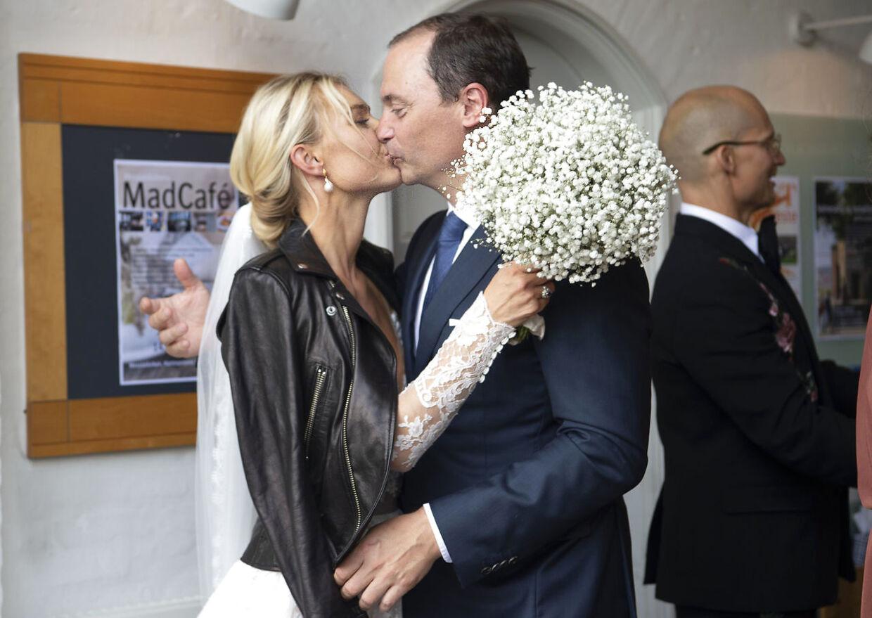 Ministeren stjæler et kys fra bruden, mens gommen Christian Stadil kigger væk.