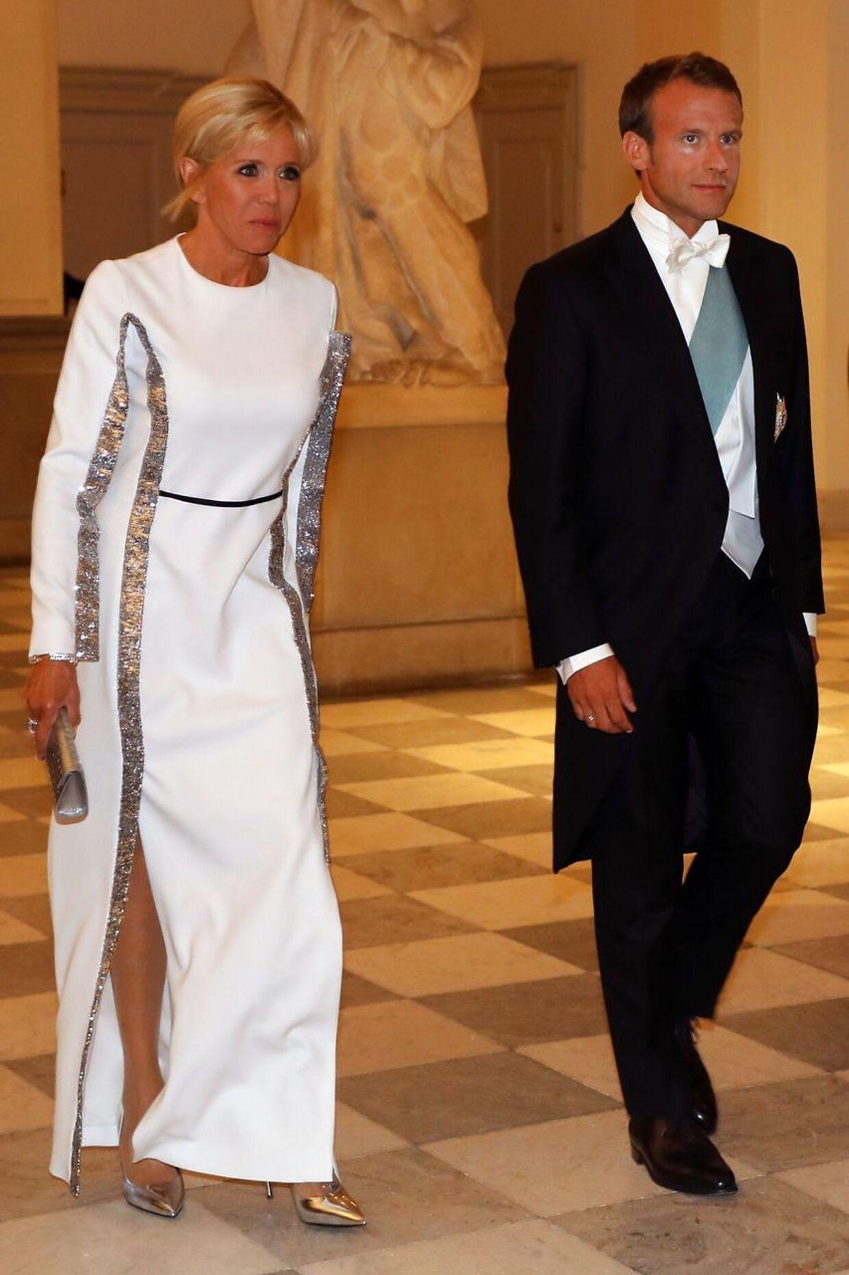»Endnu engang overrasker Brigitte Macron med sit kjolevalg. Det er ikke en typisk royal gallakjole.«»Ved første øjekast er det en klassisk hvid kjole, men ved nærmere eftersyn ser man de påsyede sølvfarvede border, der giver kjolen en tredimensionel effekt og næsten har en lille smule science fiction over sig.« »Den er helt sikkert fra et af de store franske modehuse og præsidentfruen viser med sit valg af sølvfarvede accessories sin sikre, franske stilbevidsthed.«
