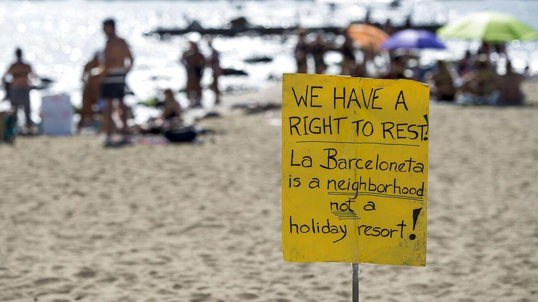 Sidste års protester mod turister lader til at have fået flere til at holde sig væk. Her et skilt på en strand ved Barcelona, der gør opmærksom på, at det ikke er et ferieparadis.