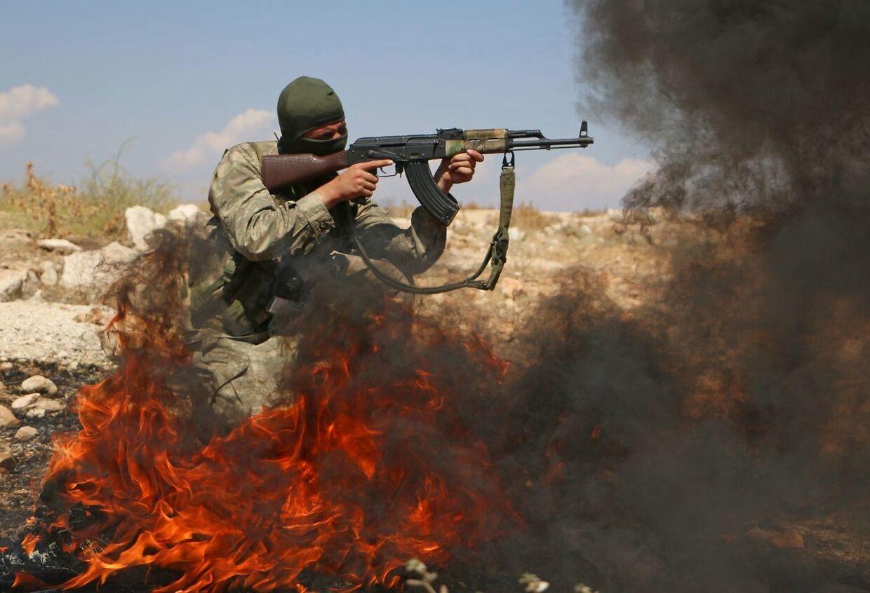 Ildkamp: Et medlem af 'Den Frie Syriske Hær' åbner ild på en ukendt lokation i Idlib-provinsen i det nordvestlige Syrien. Billedet her er fra den 11. september.