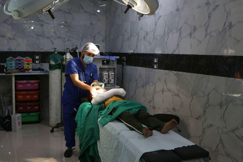 En syrisk læge behandler et kvæstet barn, der har gennemgået en operation, på et hospital i Idlib-provinsen. Billedet er fra den 10. september.