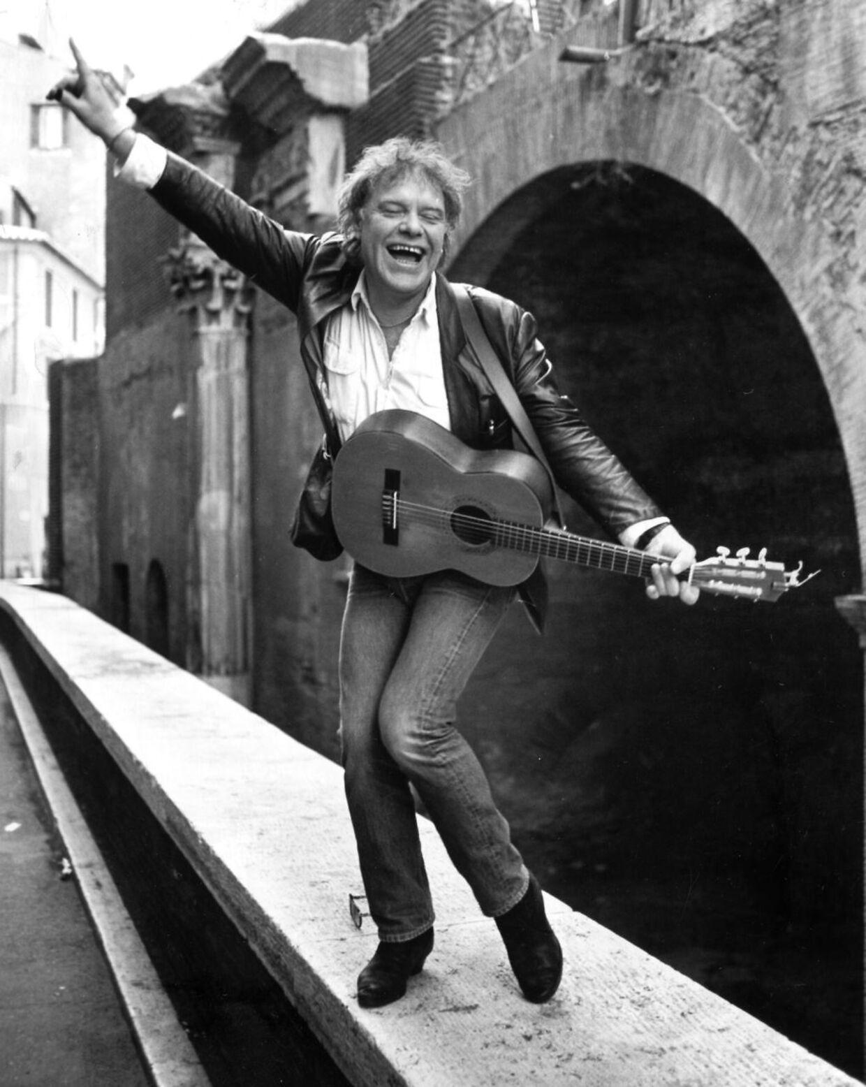 Kim Larsen, sanger, står på kanten af en bro i Rom og spiller guitar og synger.